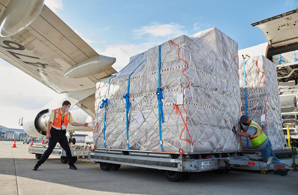 Сотрудники UPS Worldport перевозят поддоны с грузами iPhone 12, iPhone 12 Pro и iPad Air с самолета.