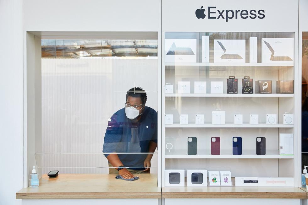 Сотрудник Apple вытирает витрину магазина Express в Apple Highland Village.