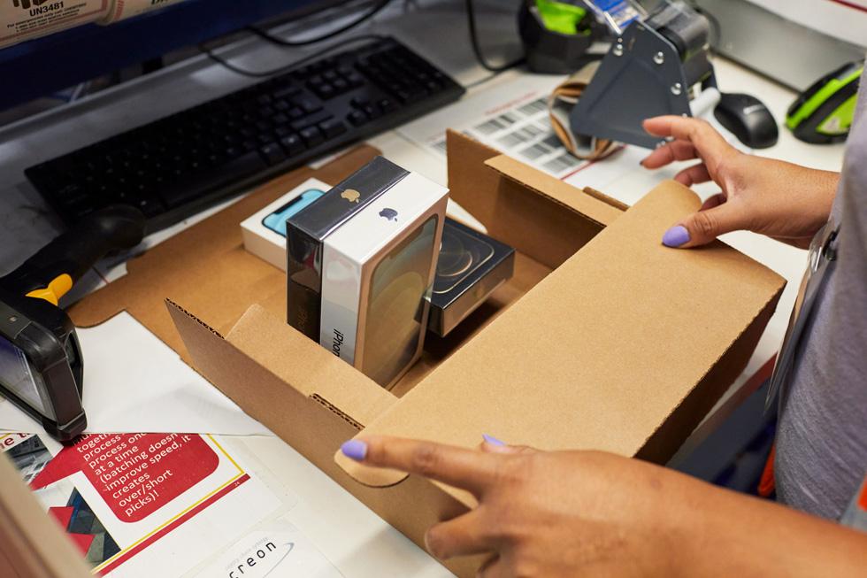 Сотрудник распределительного центра Apple упаковывает партию iPhone 12 и iPhone 12 Pro.
