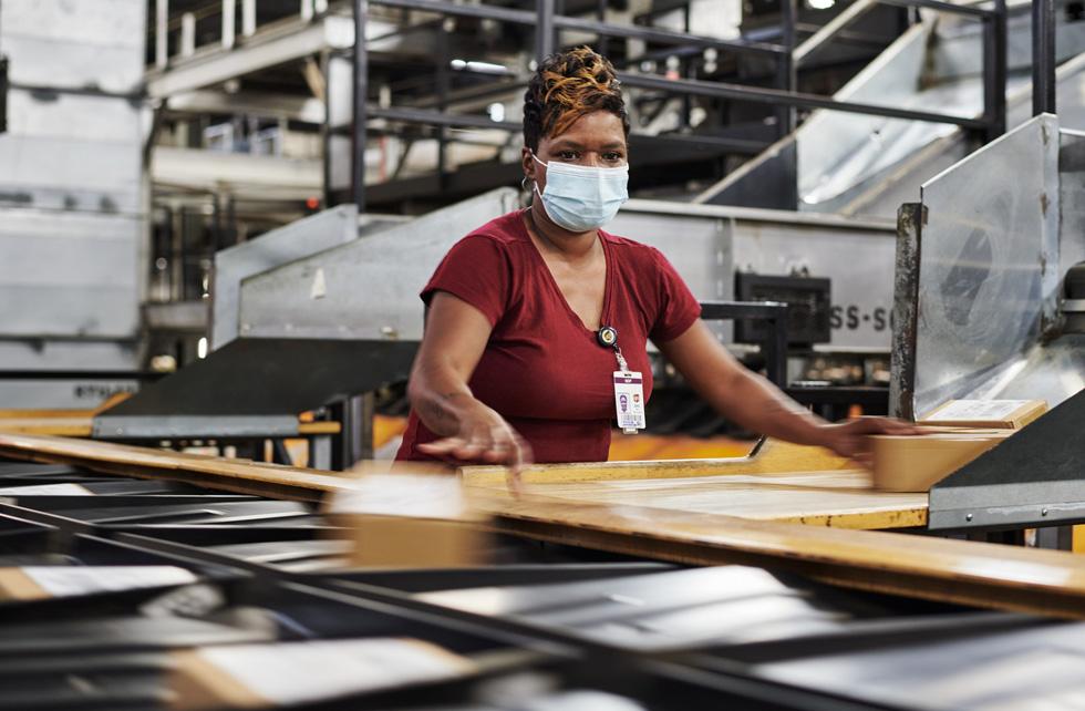 Сотрудник UPS Worldport сортирует посылки Apple для доставки.