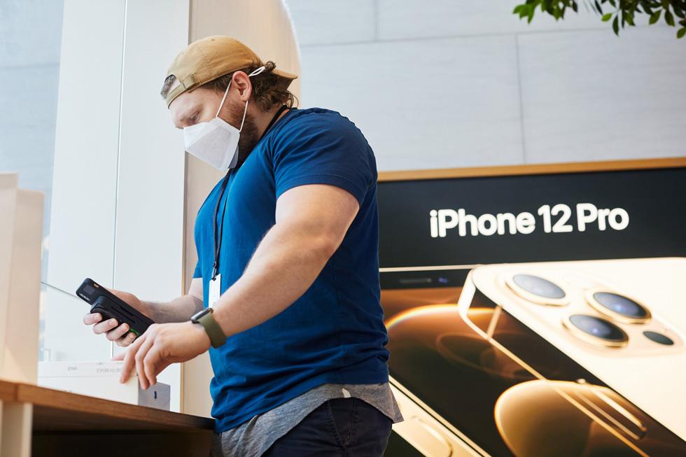 Сотрудник Apple сканирует продукты Apple в Apple Highland Village.