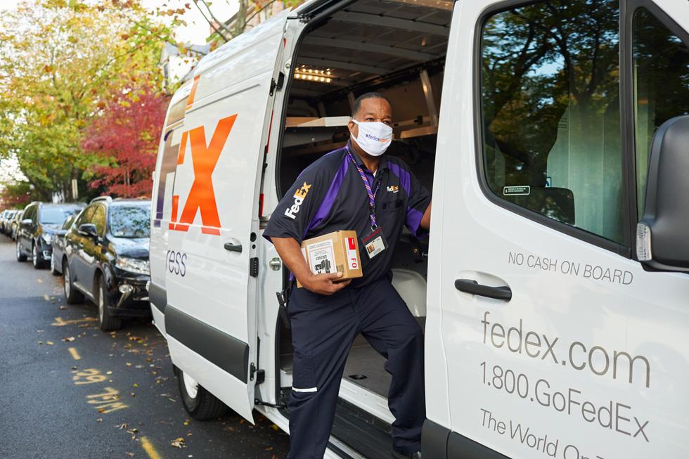 Сотрудник FedEx доставляет посылку Apple из автофургона FedEx.