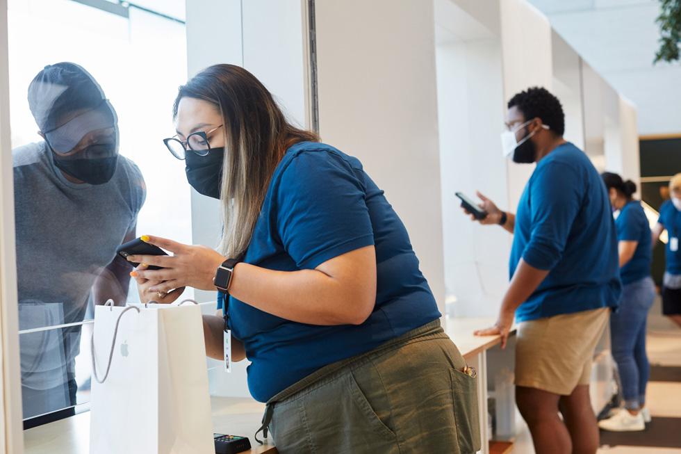 Сотрудник Apple помогает покупателю с покупкой Apple в Apple Highland Village.