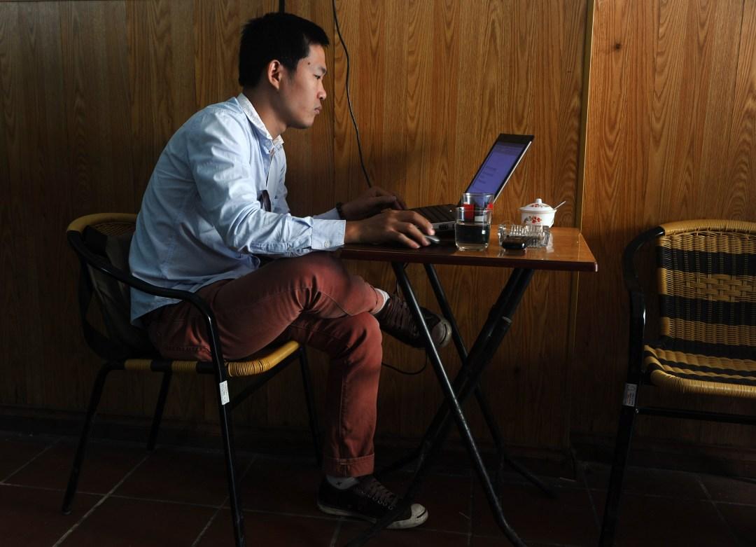 """Мужчина пользуется ноутбуком в кофейне в центре Ханоя. """"width ="""" 1080 """"height ="""" 781 """"/>   <div class="""