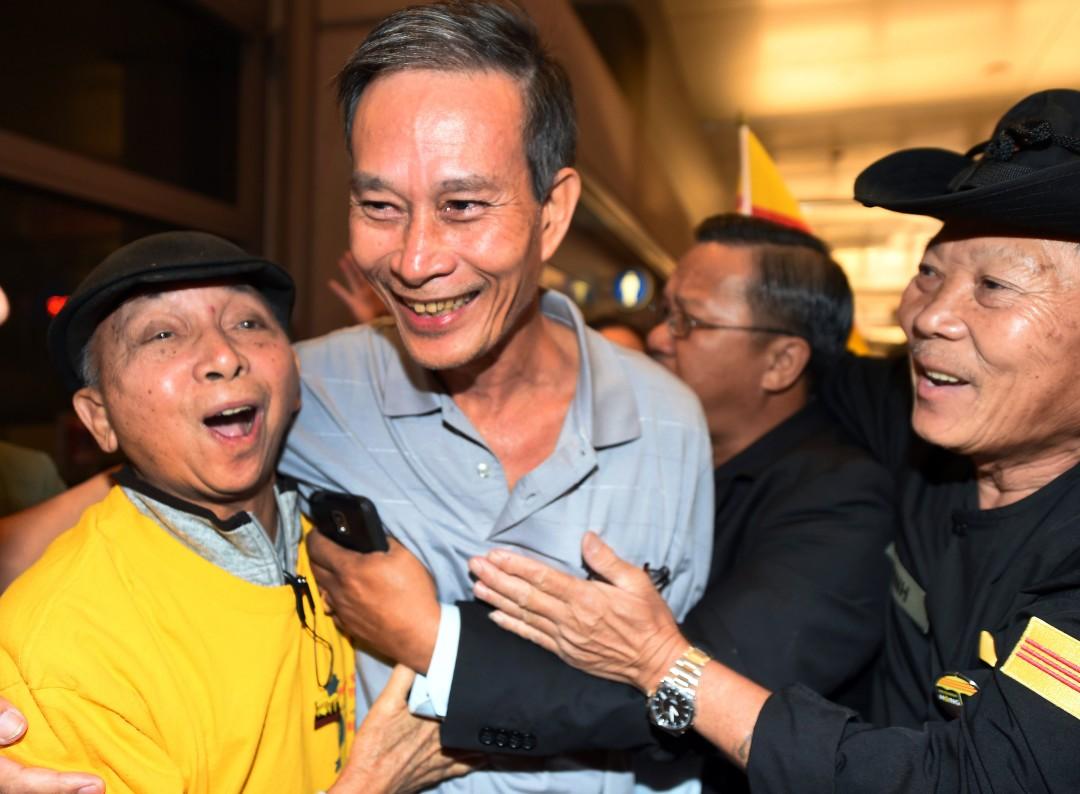 """Освобожденного вьетнамского диссидента Нгуен Ван Хай (в центре) приветствуют по прибытии в Лос-Анджелес в 2014 году. = """"1080"""" height = """"794"""" />   <div class="""