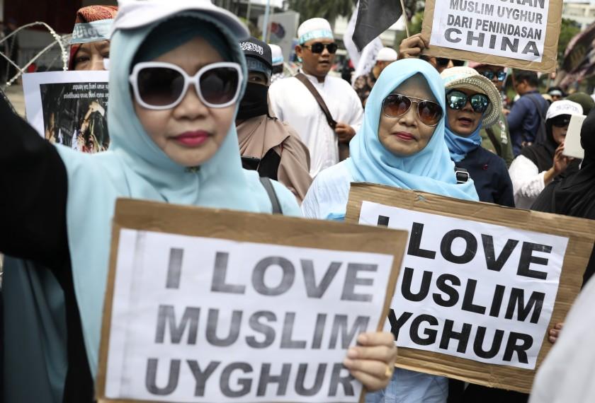 """Мусульманские женщины держат плакаты во время митинга у посольства Китая в Джакарте, Индонезия """"width ="""" 840 """"height ="""" 570 """"/>   <div class="""